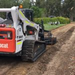 Track bobcat with grader attachment grading a new access track through the vineyards on a rural property in the swan valley
