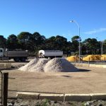 White washed sand freshly delivered on round yard with truck and dog in the background delivering a new surface for a horse arena
