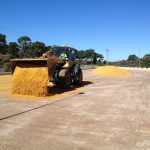 Loader spreading surface on new horse arena