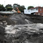 Bulk dark soil being excavated from steep site with piling used to support neighboring residents